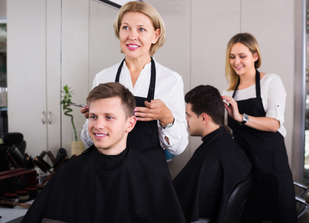 16s: Smiling senior hairdresser serving teenager guy in chair