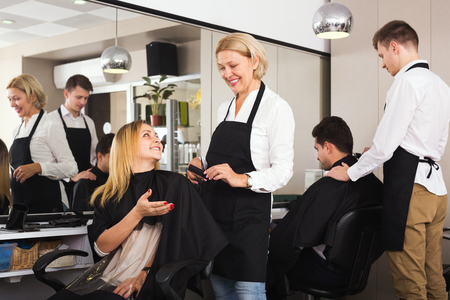 16s: Positive aged woman cutting girl hair in hairdressing saloon