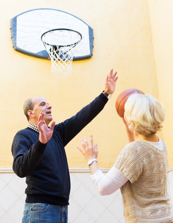 spouses: Mature spouses throwing the ball into basket
