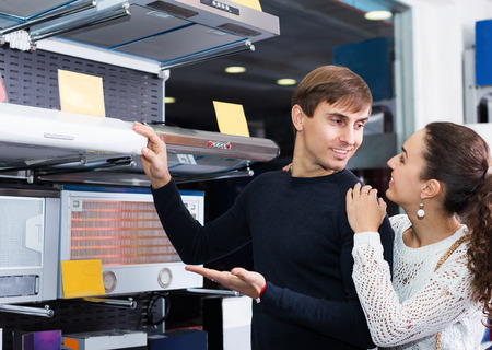 newly married couple: Newly married couple selecting kitchen hood in hypermarket and smiling Stock Photo