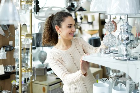 bright housekeeping: Attractive female customer buying interior lights for home in mall