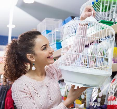 petshop: Portrait of happy girl choosing bird cage in petshop Stock Photo