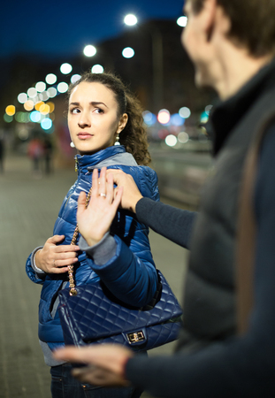 unwelcome: Tired brunette girl asking man to stop bothering her