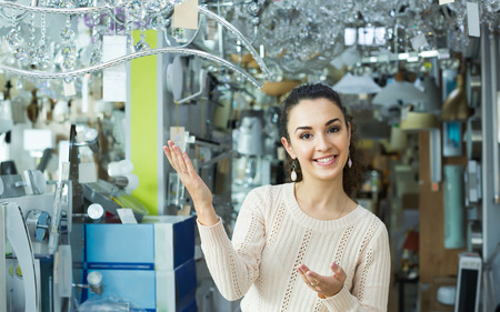 interior lighting: Young girl selecting lighting units for interior in household store Stock Photo