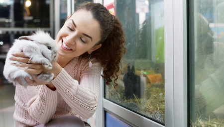 russian hamster: Portrait of smiling happy woman holding fluffy animal in hands Stock Photo