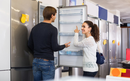 refrigerator kitchen: Middle class russian family couple choosing new refrigerator in hypermarket
