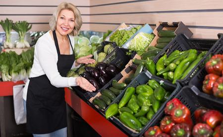 salesman: Mature female seller posing with vegetables at shop