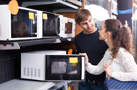 clase media: Pareja familia de clase media que elige el nuevo horno de microondas en supermercado