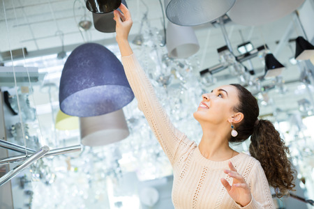 interior lighting: Woman selecting lighting units for interior in household store