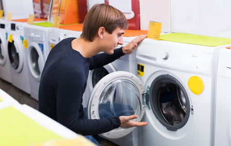 selecting: Handsome man selecting washing machine in hypermarket and smiling Stock Photo