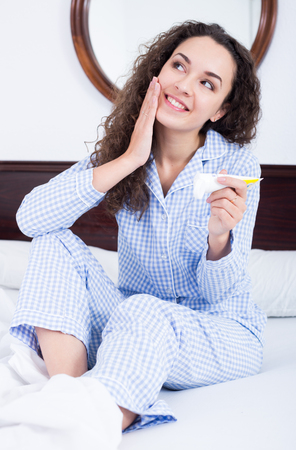 rubbing: Portrait of curly haired brunette rubbing moisturiser in face skin