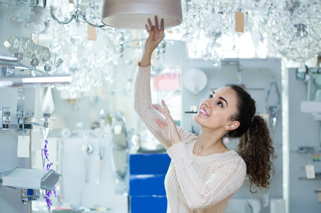 lighting: Ordinary happy european woman doing shopping in lighting shop Stock Photo