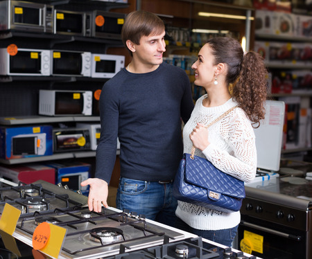 hobs: Ordinary man and woman choosing gas hobs in hypermarket and smiling