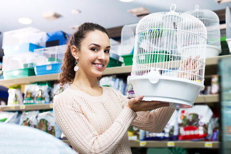 russian hamster: Smiling female customer buying cage for quinea in shop