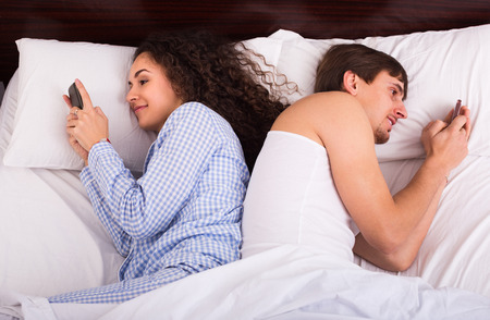 mid distance: Young family couple in bed busy with mobile phones separately