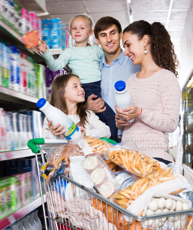 4s: Customers with children choosing dairy products in hypermarket and smiling. Focus on girl and woman Stock Photo