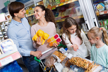 4s: Positive smiling family with two daughters purchasing yoghurts in supermarket