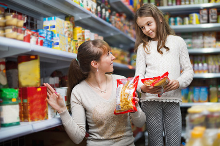 ordinary woman: Ordinary woman with girl standing near shelves with food Stock Photo