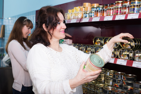 canned goods: Smiling female buyers choosing canned goods in food store