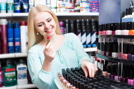 25s: Portrait of smiling young blondie selecting lipstick in store