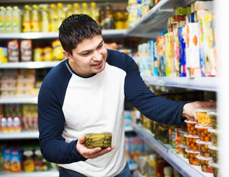 middle class: joven de clase media ordinaria compra de alimentos enlatados en el supermercado Foto de archivo