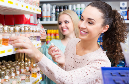 eau de perfume: Cheerful female friends buying perfume in fragrance section of supermarket
