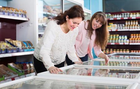 frozen meat: Happy smiling female buyers selecting frozen meat and vegetables at grocery Stock Photo