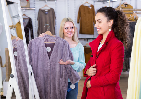 outwear: Ordinary young women shopping winter outwear at the apparel store Stock Photo