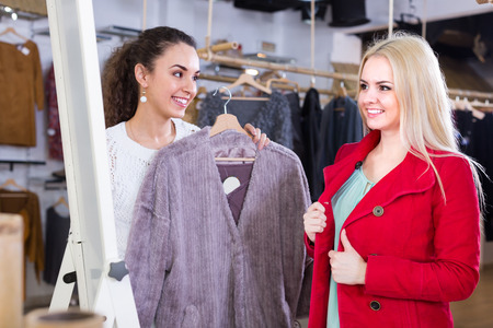 25s: Two cheerful female friends choosing warm jacket in shop and smiling Stock Photo