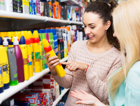 shopgirl: Cheerful brunette offering friend hair styiling spray in beauty store Stock Photo