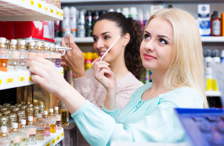 eau de perfume: Cheerful woman buying perfume in fragrance section of supermarket Stock Photo