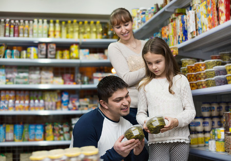 tinned: Happy young smiling parents with little girl buying tinned food at grocery