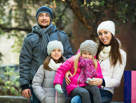 ittle: Winter portrait of cheerful smiling adults with little daughters . Focus on woman and ittle girl