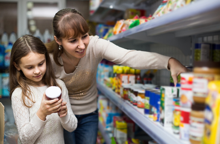 canned goods: Smiling spanish  female with daughter choosing canned goods in food store