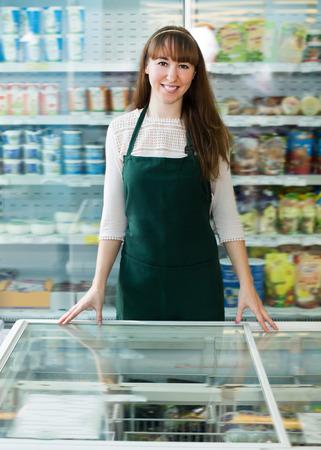 shopgirl: Girl standing near fridge with frozen goods in supermarket