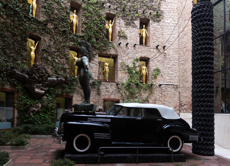 surrealist: FIGUERES, SPAIN - JANUARY 03, 2016: Courtyard of The Dali Theatre and Museum (Teatre-Museu Dali) with figurines and black car installation, Catalonia