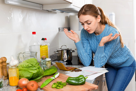 cheerless: Unhappy cheerless displeased girl reading banking documents in home kitchen Stock Photo
