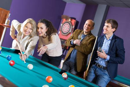 clase media: gente de clase media positivos que tienen piscina juego en el club de billar Foto de archivo