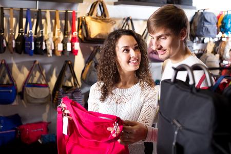 shopgirl: Positive female shopgirl helping young man to select handbag in store