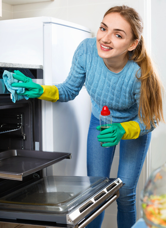 snuff: Positive adult girl in gloves removing snuff in oven
