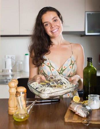 fryingpan: Woman cooking fish with ingredient  and smiling at home kitchen