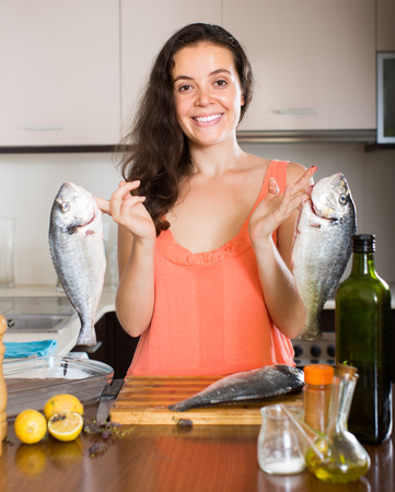 gilthead bream: Happy young smiling woman cooking fish in home kitchen Stock Photo