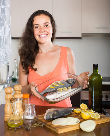 fryingpan: Smiling young brunette woman putting pieces of lemon in fish at home kitchen