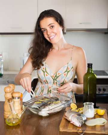 fryingpan: Young smiling brunette woman putting pieces of lemon in fish at home kitchen