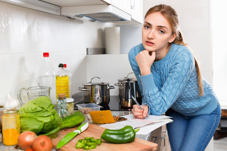 householder: Unhappy displeased girl reading banking documents in home kitchen