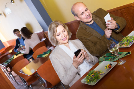 taking a wife: Positive european senior couple busy with phones on date in cafe Stock Photo