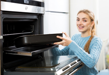 18's: Positive woman placing roasting tray in kitchen oven and smiling