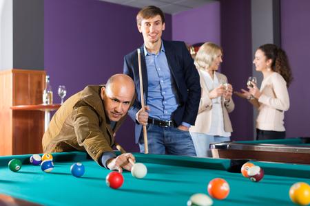 pool game: Smiling people having pool game in billiard club