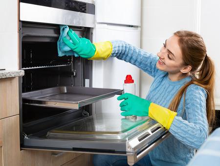 tabaco: La muchacha adulta positiva alegre en quitarse los guantes tabaco en el horno Foto de archivo