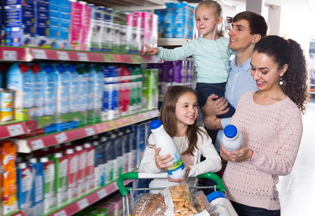 4s: Clients with children choosing dairy products in hypermarket and smiling. Focus on girl Stock Photo